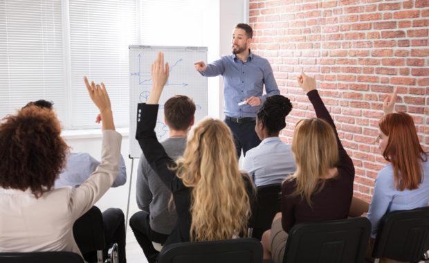Adultes levant la main en cours